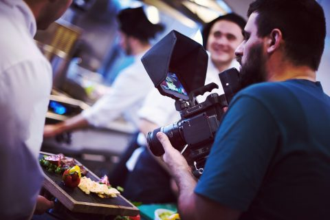 videographer recording while team cooks and chefs preparing meal